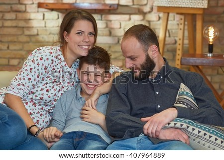 Happy family sitting on sofa at home, smiling, embracing.