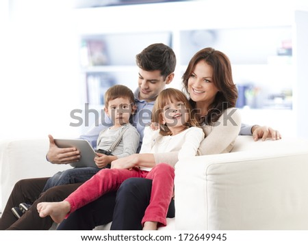 Happy family sitting on sofa in living room. - stock photo