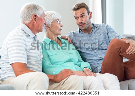 Happy family sitting on sofa in their living room - stock photo