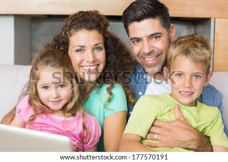Happy family sitting on sofa with laptop at home in living room - stock photo