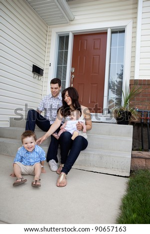 Happy family sitting on steps in front of house - stock photo