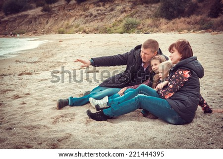 Happy family sitting on stony beach