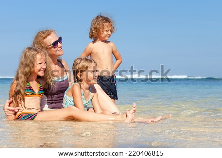 Happy family sitting on the beach at the day time