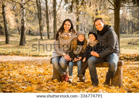 Happy family sitting on the bench, while walking in the autumn park - stock photo