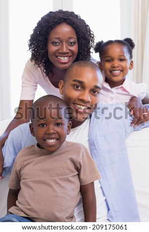 Happy family sitting on the couch together at home in the living room - stock photo