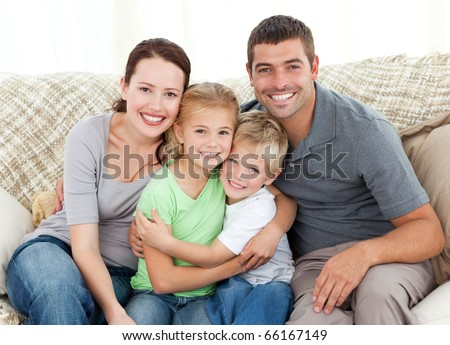 Happy family sitting on the sofa at home - stock photo