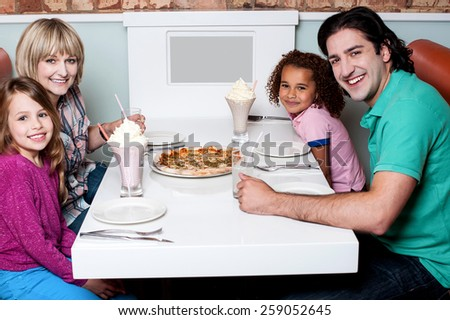 Happy family sitting together in a restaurant - stock photo