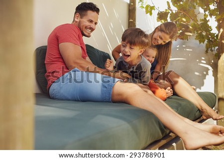 Happy family sitting together in the backyard, having fun. Father and mother playing with their kids while sitting in patio. - stock photo