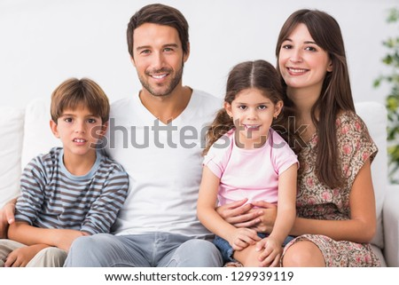 Happy family sitting together on the couch - stock photo