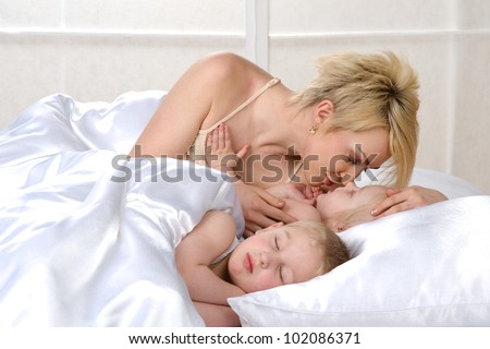 Happy family sleeping together on bed at home - stock photo