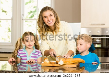 Happy family slicing bread in the kitchen