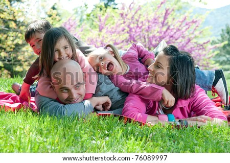 Happy family smiling and having fun outdoors - stock photo