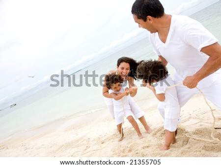 happy family smiling and having fun outdoors pulling a rope - stock photo