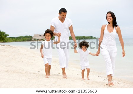 happy family smiling and walking along a beach - stock photo