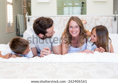 Happy family smiling at camera at home in bedroom - stock photo