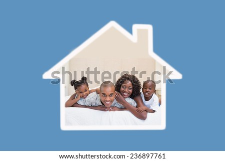 Happy family smiling at camera together on bed against blue background with vignette - stock photo