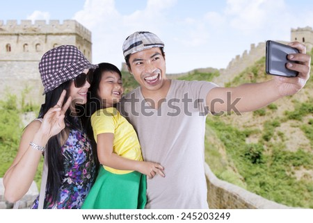 Happy family smiling at the camera phone while taking pictures together in the Great Wall - stock photo
