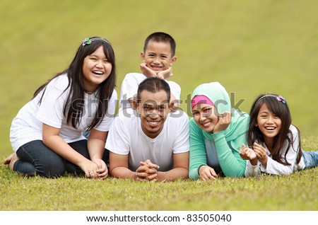 Happy family smiling having a great day in park - stock photo