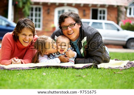 happy family smiling in a portrait of a mum and dad with their two kids - stock photo