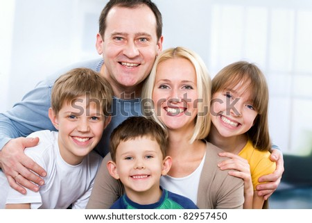 Happy family smiling looking at camera - stock photo