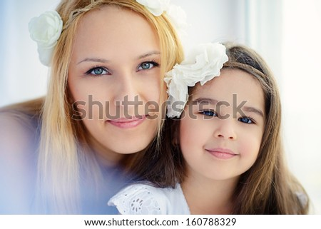 Happy family: smiling mother and her cute little daughter close up