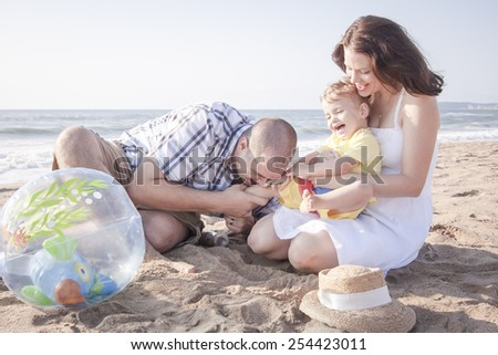 Happy family spending quality time at beach - stock photo