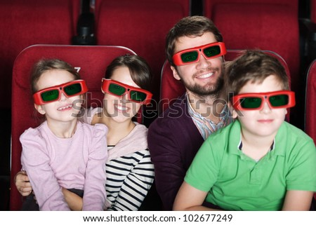 Happy family spending time in 3D movie theater - stock photo