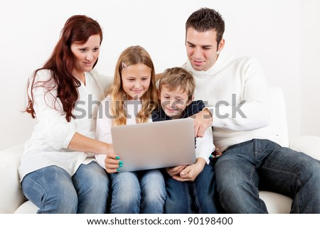 Happy family spending time together and using laptop at home - stock photo