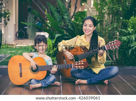 Happy family spending time together at home. Asian mother with daughter playing classic guitar and looking at camera. Vintage picture style. Positive human emotion. - stock photo