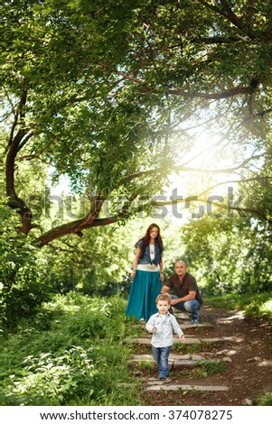 Happy Family Spending Time Together Outdoors. Pregnant Woman, Man and Cute Little Boy. Natural Colors. Selective Focus on a Kid. Sunshine Flare. - stock photo