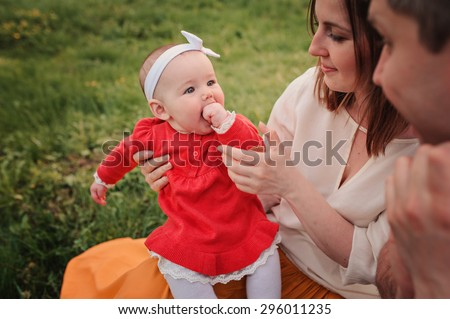 happy family spending tome together on the walk with baby daughter in summer park - stock photo