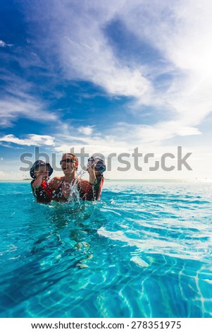 Happy family splashing in blue infinity  swimming pool of a tropical resort - stock photo