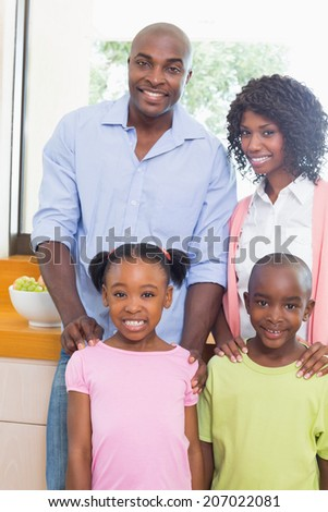 Happy family standing and smiling at camera at home in the kitchen
