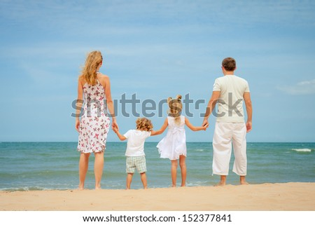 Happy family standing at the beach in the day time - stock photo