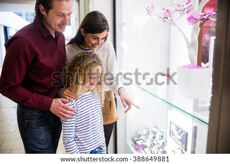 Happy family standing in front of shop window and looking at the wrist watch - stock photo