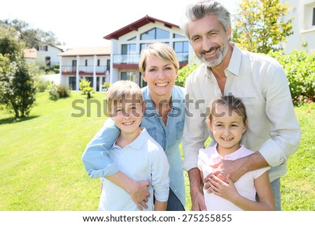 Happy family standing in home private garden - stock photo