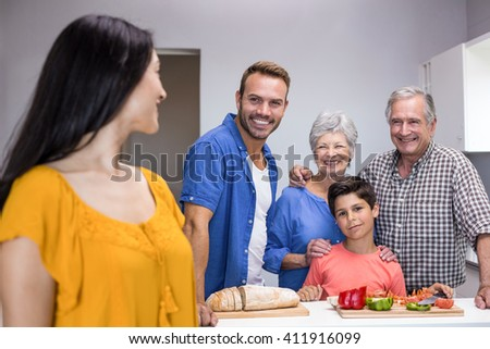 Happy family standing in the kitchen at home - stock photo