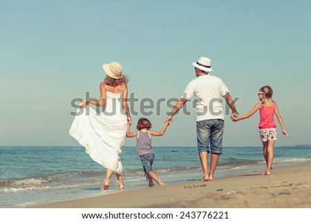 Happy family standing on the beach at the day time. Concept of friendly family. - stock photo