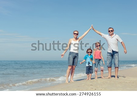 Happy family standing on the beach at the day time. Concept of friendly family.