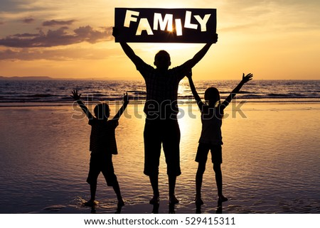 "Happy family standing on the beach at the sunset time. Parent  hold in the hands  inscription ""Family"". Concept of happy family."