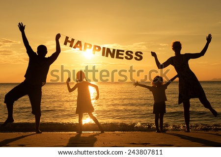 "Happy family standing on the beach at the sunset time. Parents hold in the hands  inscription ""Happiness"". Concept of friendly family."