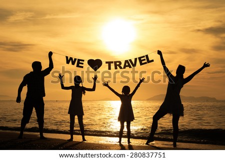 """Happy family standing on the beach at the sunset time. Parents hold in the hands  inscription """"We love travel"""". Concept of friendly family. - stock photo"""