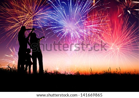 happy family standing on the hill and watching the fireworks - stock photo