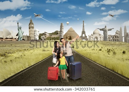 Happy family standing on the road while carrying luggage and looking at famous landmarks - stock photo