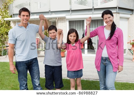 Happy family standing together holding hands outside their home - stock photo