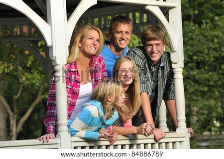 happy family standing together in a gazebo in the park - stock photo