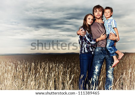 Happy family standing together in the wheat field over beautiful cloudy sky. - stock photo