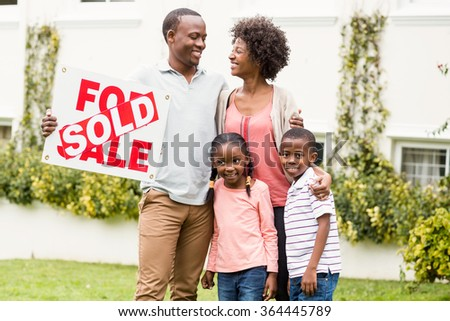 Happy family standing together while holding a sold sign - stock photo