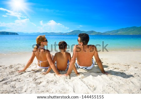 Happy family sunning on the beach on the background of the islands. - stock photo