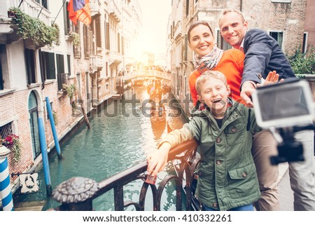 Happy family take a self photo on the bridge over Venecian channel - stock photo